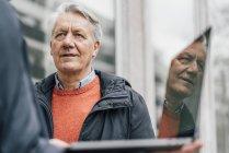 Senior man looking at man holding laptop outdoors — Stock Photo