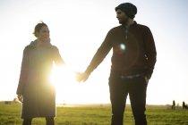 Ласкавий молодий пара стоячи рука об руку на луг на заході сонця — стокове фото