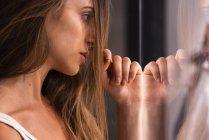Серйозний привабливий молода жінка, спираючись на скло області — стокове фото