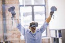 Portrait d'un homme d'affaires afro-américain avec des lunettes de réalité virtuelle et des gants de boxe au bureau — Photo de stock