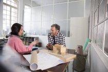 Коллеги обсуждают архитектурную модель в офисе — стоковое фото