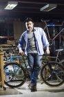 Портрет уверенного человека в велосипедной мастерской — стоковое фото