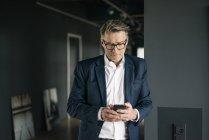 Homem de negócios maduro que está no escritório usando o telefone de pilha — Fotografia de Stock