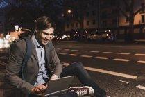 Uomo d'affari sorridente utilizzando il computer portatile sulla strada urbana di notte — Foto stock