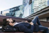 Uomo d'affari sdraiato sulla panchina fuori dall'edificio per uffici — Foto stock