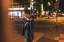 Joven empresaria al teléfono por la noche - foto de stock