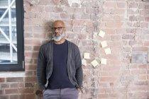 Портрет африканского фрилансера, прислонившегося к стене в лофте — стоковое фото