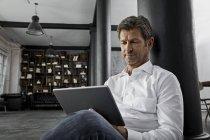 Mature man sitting on the floor using digital tablet in loft flat — Stock Photo