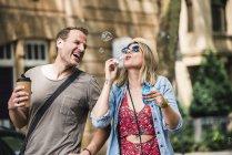 Casal feliz com café para ir soprar bolhas de sabão na cidade — Fotografia de Stock