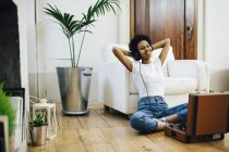 Young african american woman sitting on ground and listening music from record player, using headphones — Stock Photo