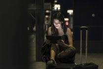 Mulher nova de sorriso com a tabuleta que espera na estação em a noite — Fotografia de Stock