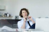 Easygoing uomo d'affari seduto in ufficio, bere succo di frutta — Foto stock