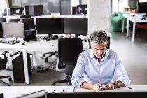 Зрілі бізнесмен сидячи на столі в офісі і за допомогою смартфона — стокове фото