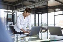 Donna d'affari in piedi al tavolo di vetro in ufficio utilizzando il computer portatile — Foto stock