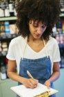 Жінка в магазині записує нотатки на дошці. — стокове фото
