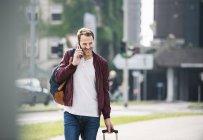 Homem sorridente com mala rolante no celular da cidade — Fotografia de Stock