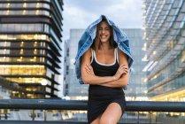 Портрет щасливого молодої жінки в чорному вбранні в місті в сутінках — стокове фото