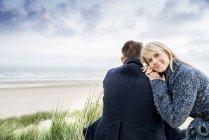 Couple sitting in dunes — Stock Photo