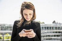 Mensajería de texto de mujer sonriente en la terraza de la azotea - foto de stock