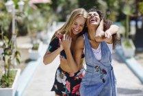 Две смеющиеся молодые женщины летом на улице — стоковое фото