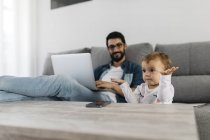 Father using laptop at home, daughter playing in the foreground — Stock Photo