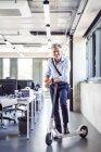 Ritratto di felice maturo uomo d'affari cavalcando scooter in ufficio — Foto stock