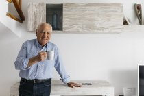 Senior man having a coffee while relaxing at home, looking at camera — Stock Photo