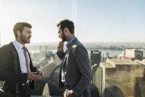 США, Нью-Йорк, два бизнесмена разговаривают на смотровой площадке Рокфеллеровского центра — стоковое фото