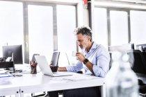Зрелый бизнесмен сидит за столом в офисе с ноутбуком и пьет кофе — стоковое фото