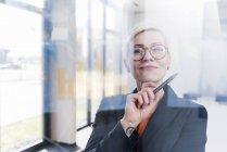 Портрет довіреної бізнесменки за скляною панеллю в офісі — стокове фото