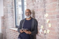 Portrait of smiling african american freelancer with tablet leaning against wall in a loft — Stock Photo