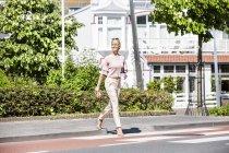 Donna sorridente che attraversa una strada — Foto stock
