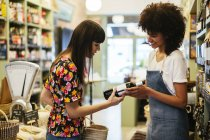 Помічник магазину консультування замовника з пляшкою вина в магазині — стокове фото