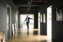 Empresario montando longboard en piso de oficina - foto de stock