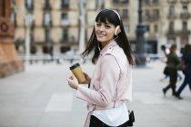 Espanha, Barcelona, mulher sorridente com café, telefone celular e fones de ouvido na cidade — Fotografia de Stock
