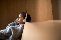 Porträt einer entspannten jungen Frau, die mit Kopfhörern auf der Couch Musik hört — Stockfoto