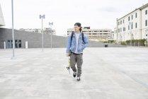 Jeune homme marchant dans la ville, portant du skateboard — Photo de stock