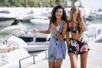 Две смеющиеся девушки на набережной летом — стоковое фото