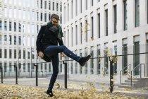 Бизнесмен играет с осенними листьями в городе — стоковое фото
