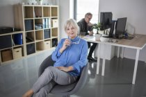 Senior businesswoman sitting in office with colleague working behind her — Stock Photo