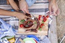 Крупним планом пара їсть смажені ковбаски і помідори на вулиці — стокове фото
