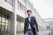 Усміхнений бізнесмен з перехресної сумці тіла в місті на ходу — стокове фото