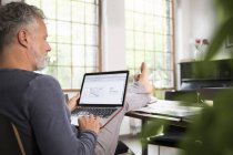 Mature man working from his home office with feet up, using laptop — Stock Photo