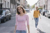 Donna che cammina in strada con amica sullo sfondo — Foto stock