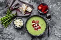 Green asparagus cream soup with strawberry, parmesan and baguette — Stock Photo