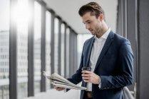 Giovane uomo d'affari in piedi in un corridoio con caffè da asporto e giornale — Foto stock