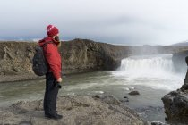 Iceland, North of Iceland, young man looking to waterfall — Stock Photo