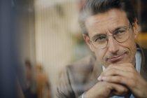 Homem de negócios maduro sentado no café, olhando pela janela — Fotografia de Stock