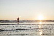 Femme heureuse dans l'eau de mer, coucher de soleil sur l'horizon ciel — Photo de stock