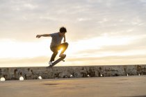 Young Chinese man skateboarding at sunsrise near the beach — Stock Photo